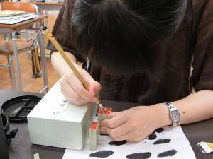 石に墨で文字を布字しています(篆刻)