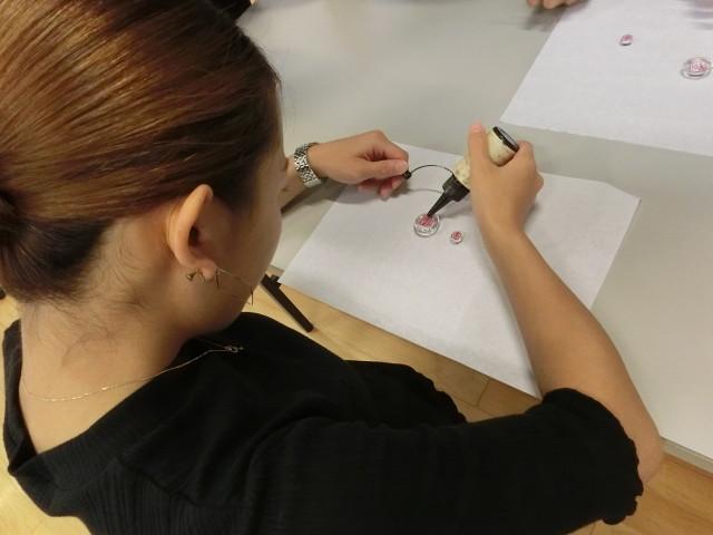 レジン液を使って磁石の頭に印を押した紙に付けています
